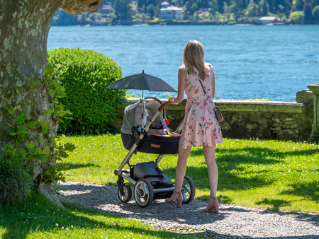 Image of young mother pushing the stroller in a park