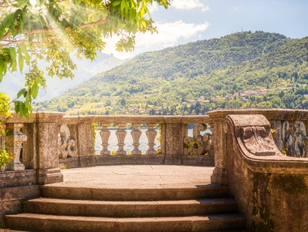 Image of Italian stone balustrade illuminated by sun rays and water in the background Archivio Fotografico - 125707334