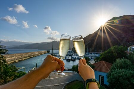 Two hands holding two glasses of champagne in front of a marina during sunset