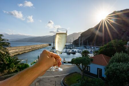 One male hand holding a glass of champagne in front of a marina during sunset