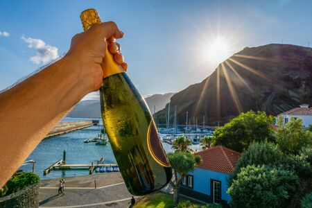 One hand holding a bottle of champagne in front of a marina during sunset