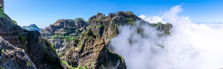Panorama image of mountains with hiking trail hit by huge clouds and blue sky, Madeira Banque d'images - 129368711