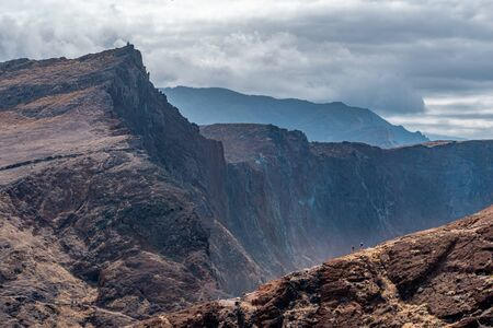 Couple hikes on rocky mountain trail with epic cliff background, Madeira Stockfoto