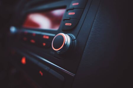 Control panel and enter button and knob on a car's dashboard, close up