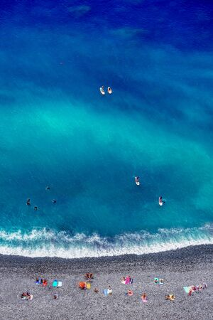 Tropical beach with colorful beach towls, people, divers and surfers - Top down aerial view drone Imagens