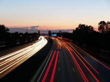 Langzeitbelichtung der deutschen Autobahn A8 bei Augsburg bei Sonnenuntergang. Standard-Bild