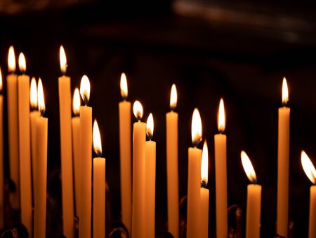 Image of many burning candles with shallow depth of field, close up.