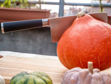 Orange hokkaido pumpkin with ax on wood free space flat lay. Top view on rustic wooden table with cutaway fresh squash. Seasonal, dieting, vegetarian cuisine concept. Free space for your text Stock Photo