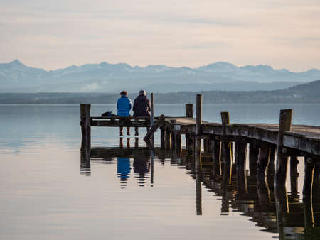 Rear view of couple sitting on wooden pier at lake ammer in bavaria with alps in the background.