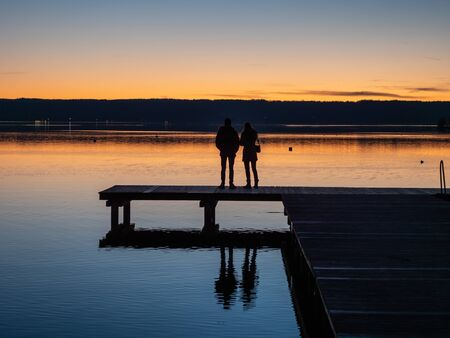 Rear view of couple standing on wooden pier at lake ammer in bavaria during sunset with alps in the background. Standard-Bild