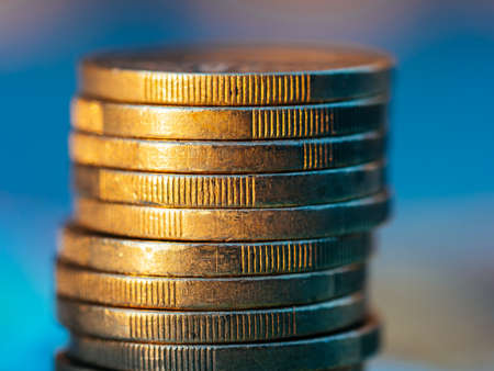 Close up view on euro coin stack on blue background. Standard-Bild
