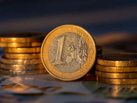 Close up view on one Euro coin with euro coin stacks on one hundret euro bill.