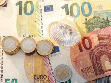 LED light bulb on euro coins and euro bills. Concept for electricity bill or savings from power supply change.