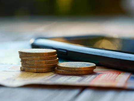 Black smartphone on euro bills and euro coins. Concept of saving money by changing smartphone contract