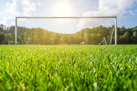 Focus on green grass of a football field with blurry goal in the background
