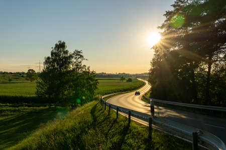 Car driving curvy road on the countryside during sunset.