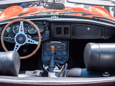 The steering wheel and dashboard of an antique classic car.