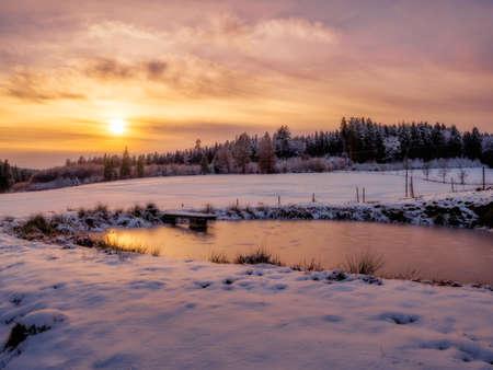 Wonderful winter landscape with frozen lake and snow during sunset Standard-Bild