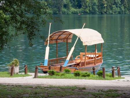Beautiful wooden boat on famous Bled Lake in Slovenia. Bled Lake, known for its castle and island, is a popular travel destination. Tourist boats are used for summer sightseeing tours on the blue lake