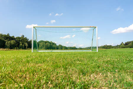 Focus on green grass of a football field with blurry goal in the background.
