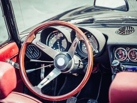 The steering wheel and dashboard of an antique classic car