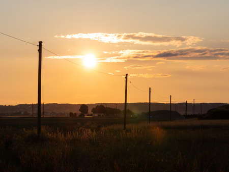 Sunset with the silhouette of high voltahe power posts. Beautiful natural landscape in the summer time Standard-Bild