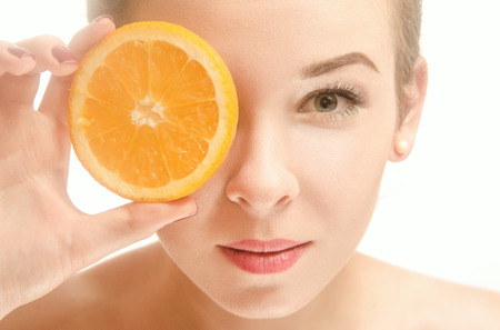 Beautiful young seminude woman of European appearance holds an orange in front of her eyes, standing on white background