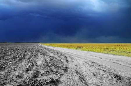 Blauer Himmel in den Wolken und in der Staubstraße vom Feld