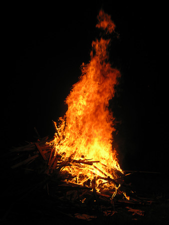 bonfire night: Bright orange flames in the darkness of the boards Stock Photo
