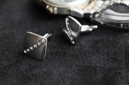 Silver cufflinks with crystals lie one after another on a black canvas near the clock Stok Fotoğraf