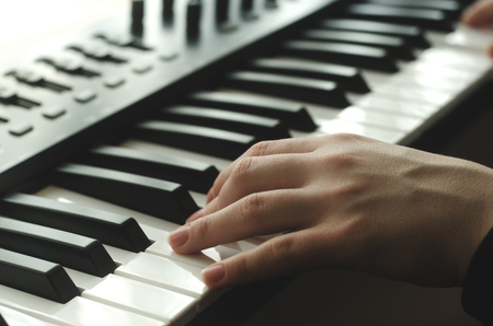 electronic music: A woman is playing a synthesizer. In the frame one hand, side view Stock Photo