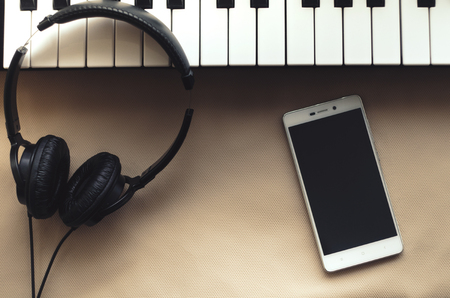 electronic music: The headphones are on the synthesizer. The synthesizer stands on a beige background. Nearby is the phone. View from above. Stock Photo