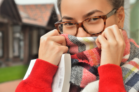Portrait of an Asian girl in glasses, she screwed her face with a scarf, only her eyes and hands are visible. The hair is tied to the knot. Standing on the street. Bright colours. Horizontal photo
