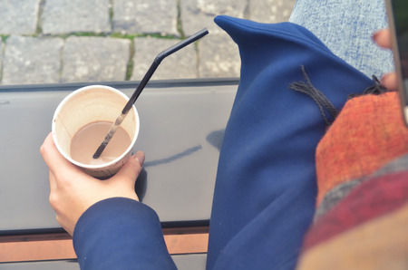 A womans hand holds a paper cup of coffee. From the cup, stick out the straw. The cup stands on the bench. You can see a paving stone and a womans leg in jeans