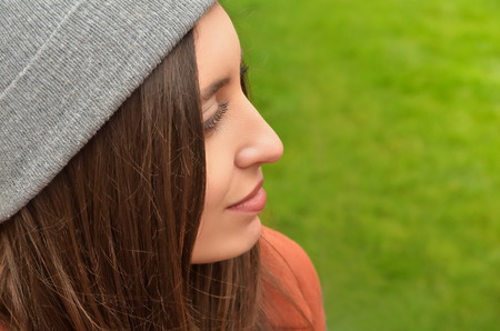 Portrait of a beautiful young European woman against green background. Dressed in a hat, turned into a profile. Easily smiles