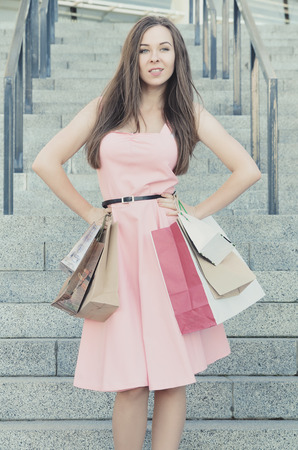 A beautiful young woman with purchases after shopping, stands with paper bags and looks away. Dressed in a dress, hands in the sides