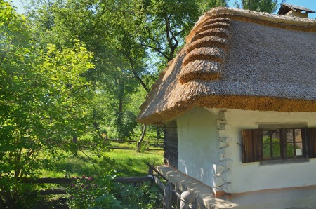 Beautiful white-fronted house with a stony roof among the trees in summer