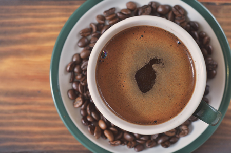 A cup of strong coffee with a foam on a saucer with coffee beans on a wooden background. Texture, background, wallpaper Stock Photo