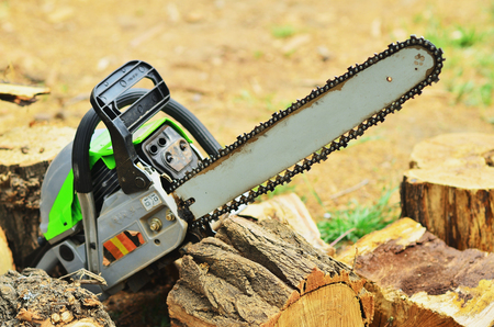 The big working chainsaw lies on the hemp and chopped wood Stock Photo