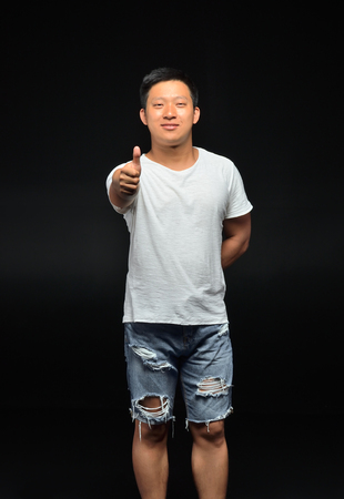 Portrait of a male Asian student of appearance on a black background that shows a thumbs up