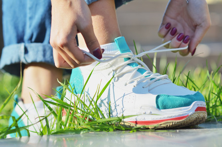 Young girl wearing jeans tying shoelaces on sneakers standing on green grass side view close-up horizontal photo, Sunny day