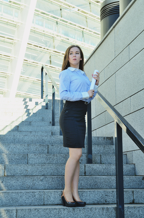 Beautiful young business woman standing near high architecture in shoes and short black skirt, looking into the distance, vertical photo