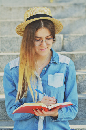 A young girl student dressed in a hat and a denim shirt writes ideas in a notebook