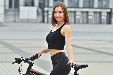 Portait of young girl with sport bike is walking in the city