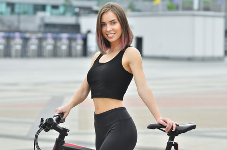 Young beautiful fitness girl with sport bike is walking in the city