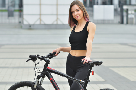 Young beautiful girl wearing a tracksuit rides a bicycle through the streets of the city