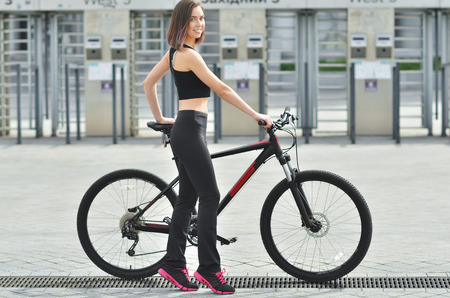 A beautiful young girl in a black T-shirt and black sport pants is riding a bicycle through the city - Outdoors