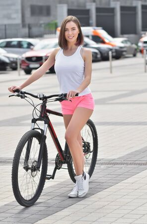Pretty fit girl is riding on bike a bicycle through the streets of the city Reklamní fotografie