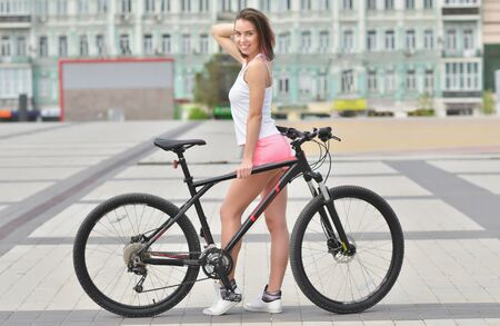 Girl in white pink tracksuit rides a bicycle on the city road. Healthy lifestyle concept. Sports girl with bike