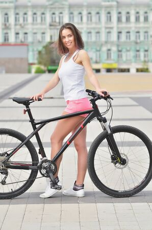 Portrait of pretty young girl with bicycle in a the city. Summer day